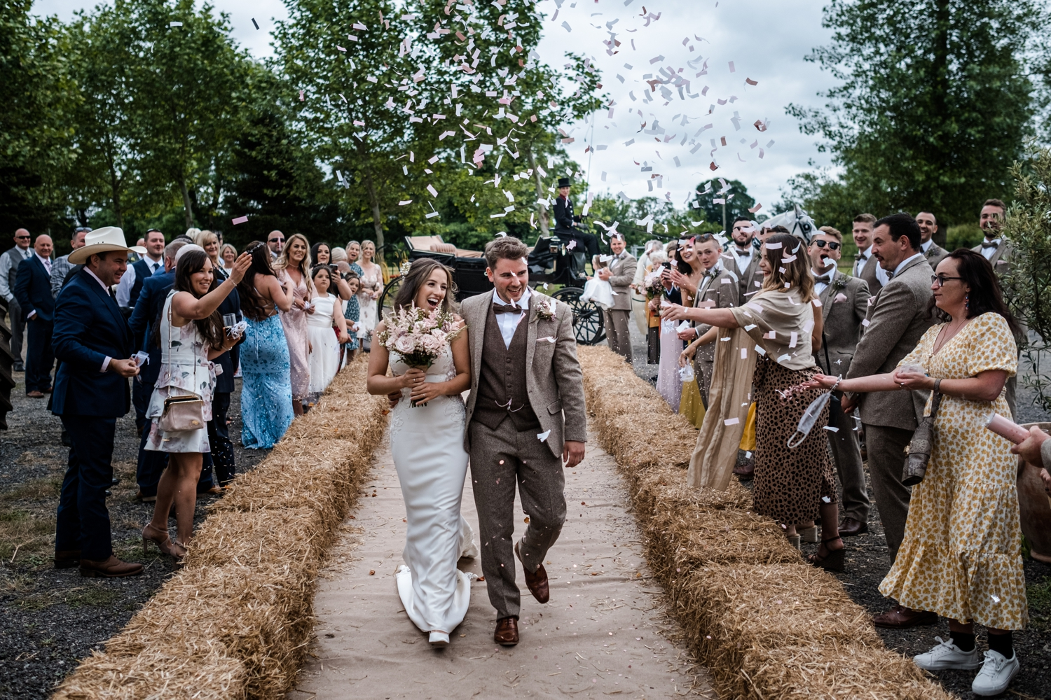Bride and groom with confetti at Welsh farm wedding