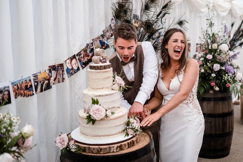 Cutting the cake at Welsh farm wedding reception