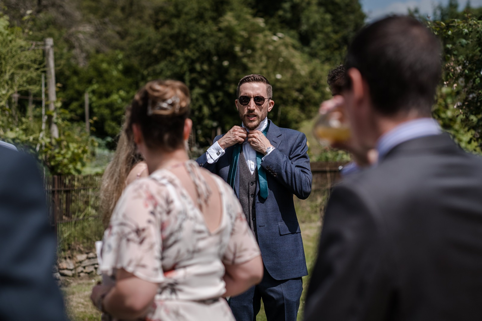 Groom puts on tie for wedding at Gants Mill