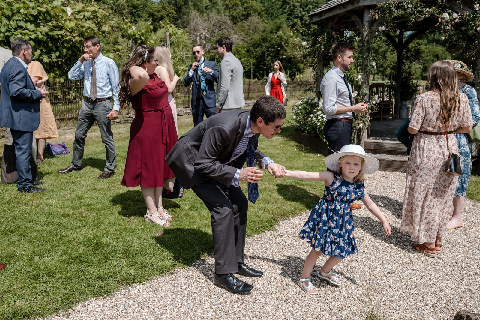 Little girl pulls Dad arms to explore gardnes at Gants Mill